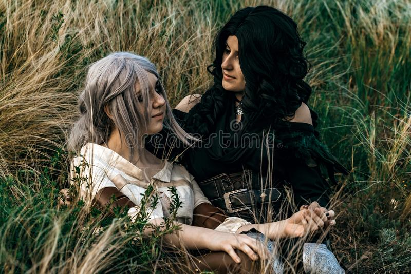 Fantasy cosplay two beautiful sit together in grass stock images