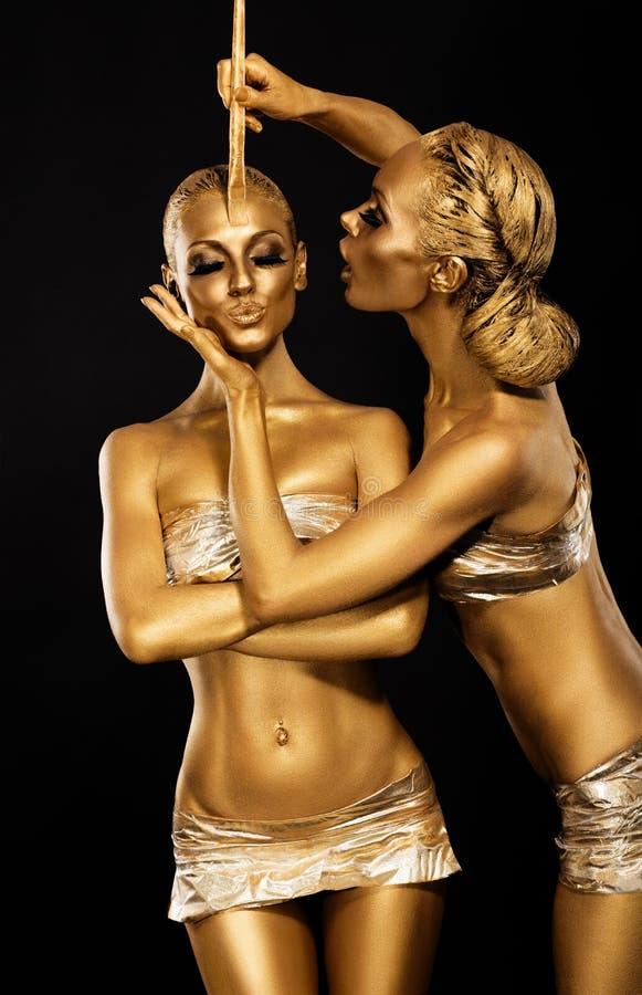 Fantasy. Creativity. Shiny Women's Gold Gilded Bodies. Arts. Bright Women's Gold Gilded Bodies. Art concept stock images