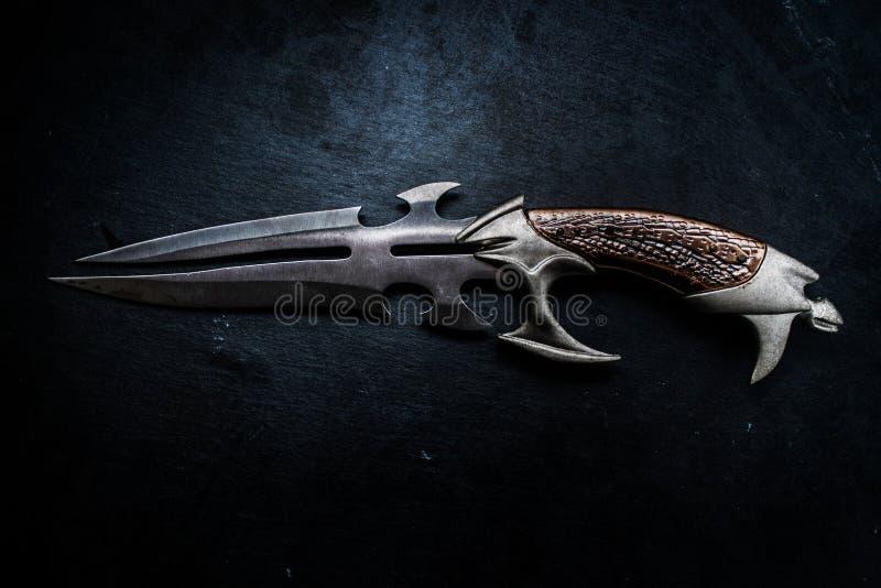 Fantasy dark blade over grunge blue background. Fantasy style dark knife closeup with grunge blue abstract background warrior concept stock photo