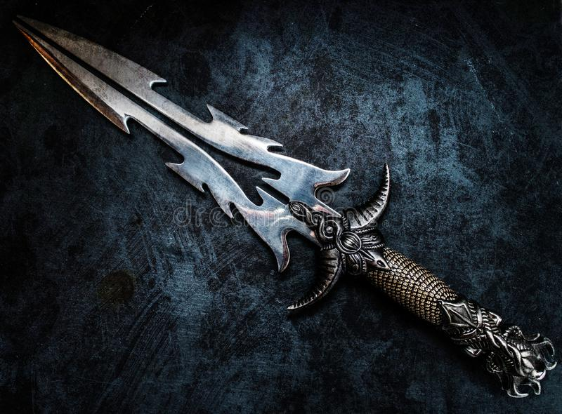 Fantasy dark blade over grunge blue background. Fantasy style dark knife closeup with grunge blue abstract background warrior concept royalty free stock photo