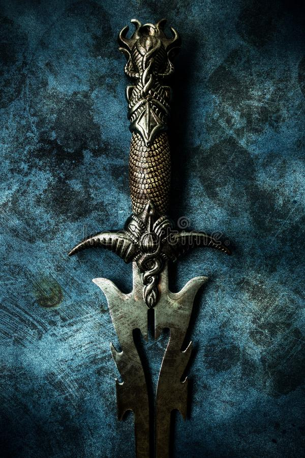 Fantasy dark sword over grunge blue background. Fantasy style dark sword closeup with grunge blue abstract background warrior concept royalty free stock photo