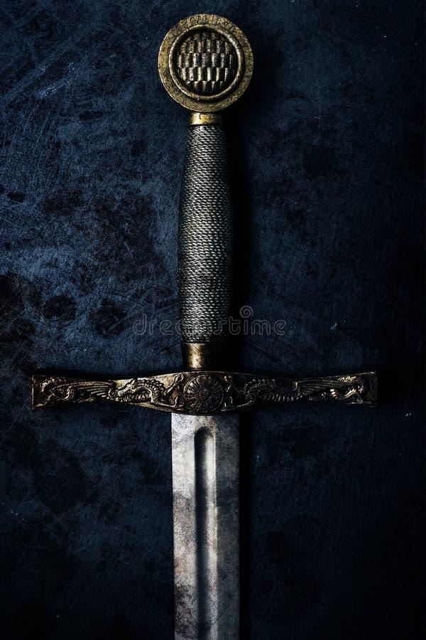 Fantasy dark sword over grunge blue background. Fantasy style dark sword excalibur closeup with grunge blue abstract background warrior concept stock photo