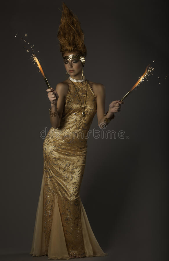 Fantasy image of flame-throwing woman in gold couture royalty free stock photography