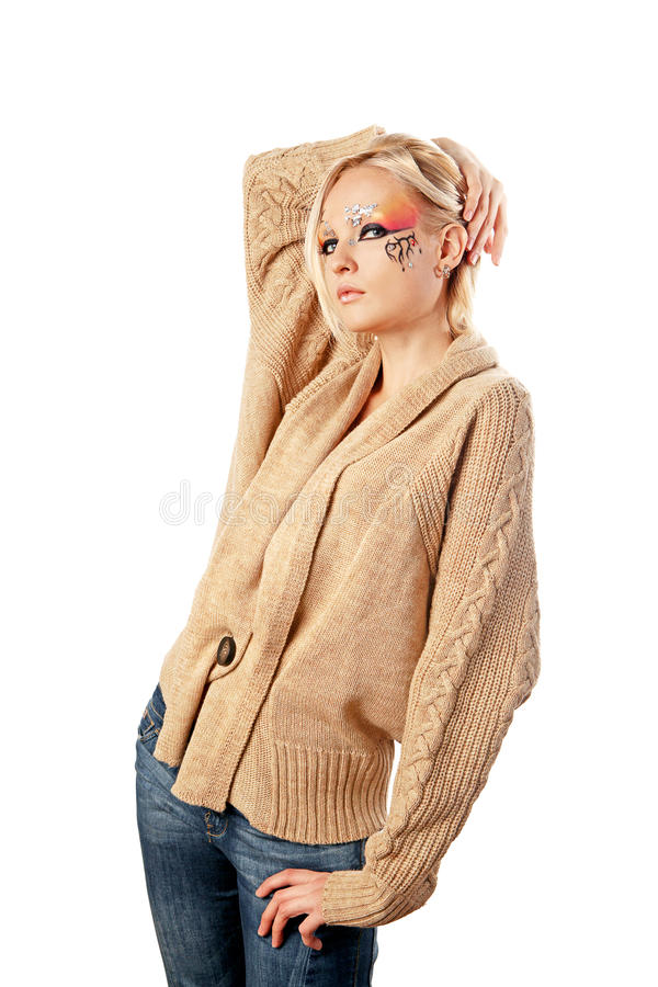 Fantasy make-up. A young pretty blond girl with a bright fantasy make-up dressed in a woolen cardigan stock photo