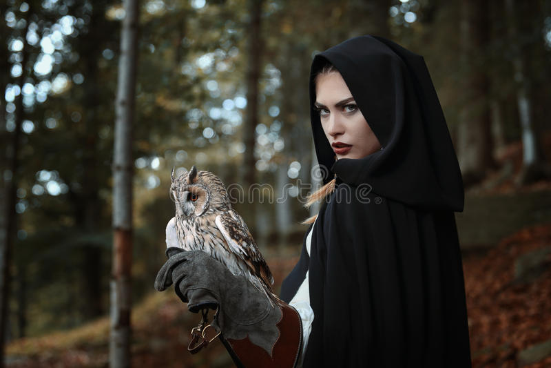 Fantasy owl master. Dark fantasy owl master. Dark hooded woman stock photos