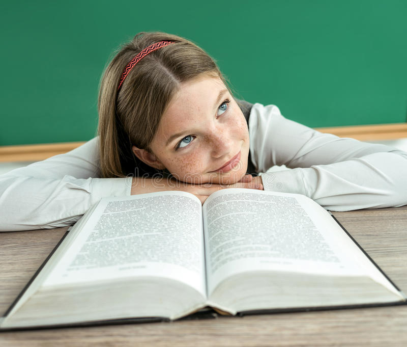 Fantasy pupil looking up as if daydreaming or thinking of something pleasant while sitting at the desk with open book. stock images
