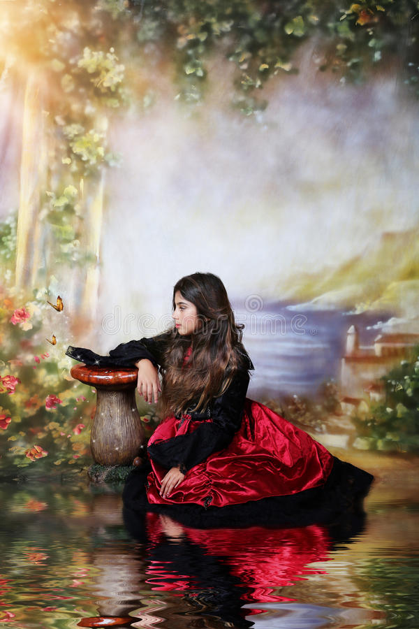 Fantasy scene. Girl in a beautiful satin gown in a fantasy and dreamy settings royalty free stock image