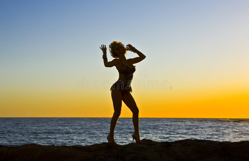 Fantasy Silhouette Dancer on Rocks at the Beach. During Sunset stock photos