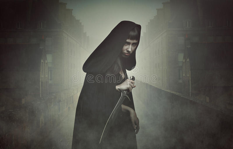 Fantasy thief in the fog. Black hooded thief with knife waiting in the fog . Fantasy and legend royalty free stock image