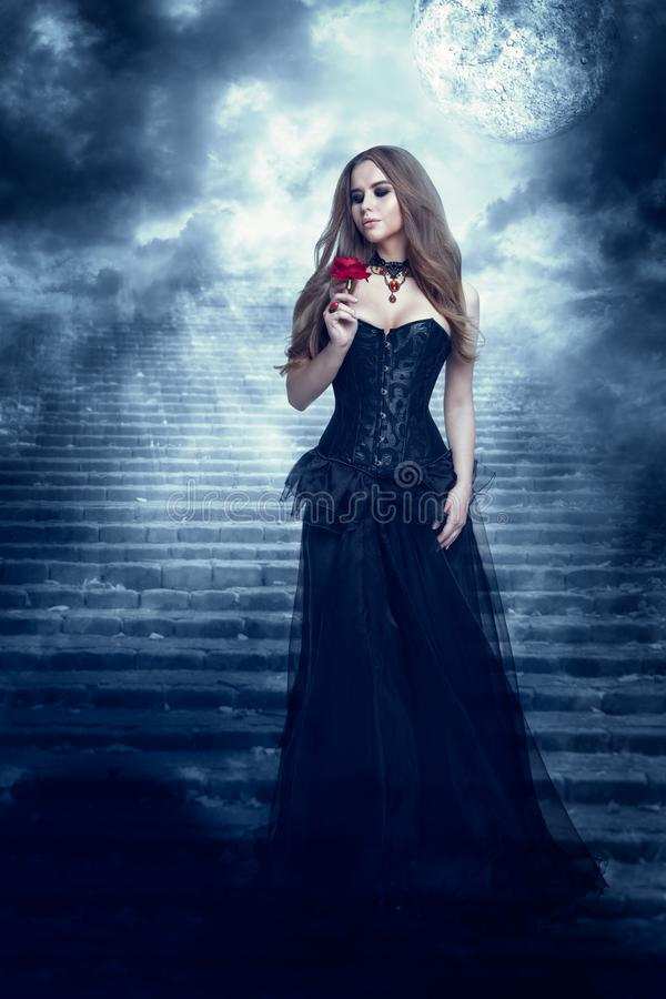 Fantasy Woman in Black Dress Smelling Rose Flower, Mystic Girl in Long Retro Gothic Gown. Blue moon royalty free stock photos