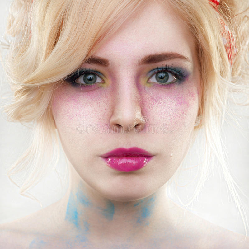 Fantasy woman with bright make-up and powder on face on grey background royalty free stock image
