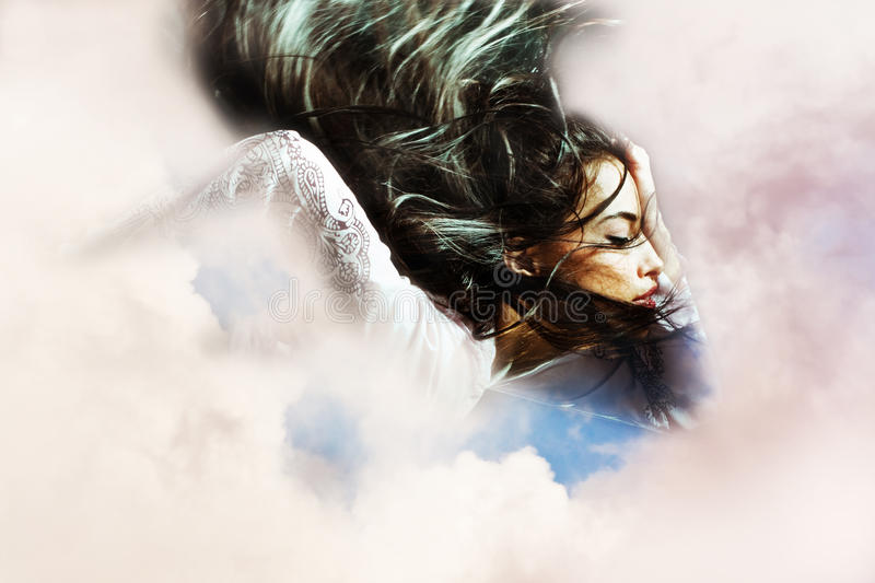 Fantasy woman flying through the clouds. Fantasy woman with long flying hair in clouds royalty free stock photography