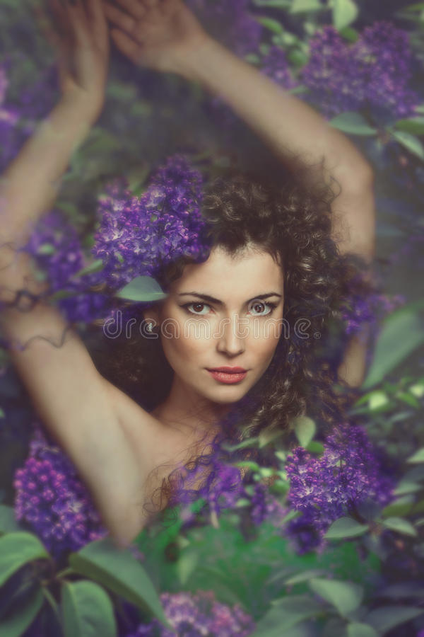 Fantasy woman. Fantasy forest fairy surrounded by flowers royalty free stock image