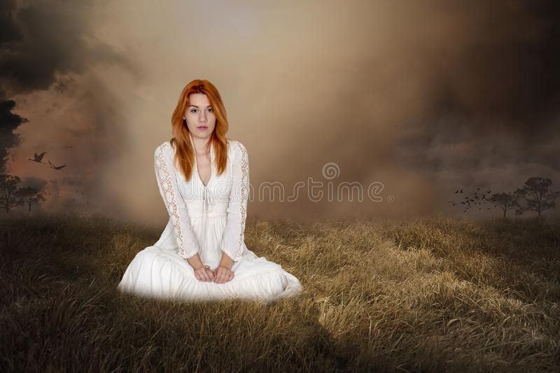 Fantasy Woman, Imagaination, Peace, Hope, Love. A beautiful young woman in a white dress sits in a grassy meadow field. Abstract concept for peace, hope, love royalty free stock photo
