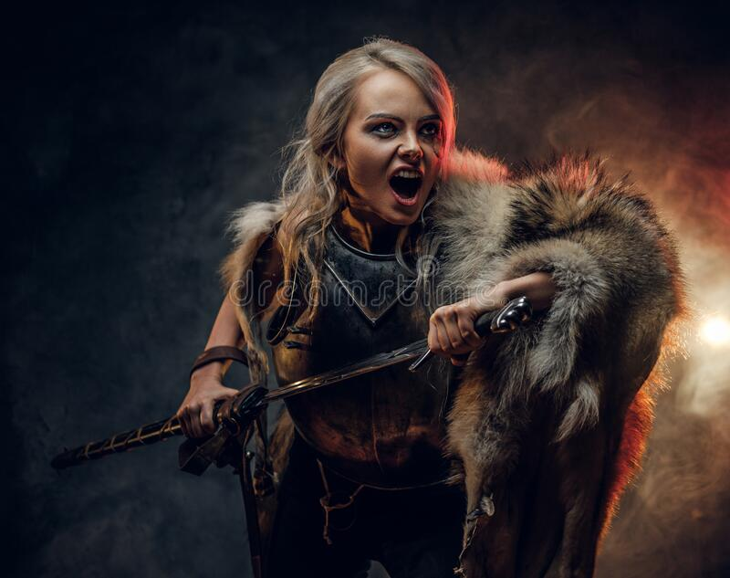 Fantasy woman knight wearing cuirass and fur, holding a sword and rushes into battle with a furious cry. Cosplayer as. Ciri from The Witcher. Studio photography royalty free stock images