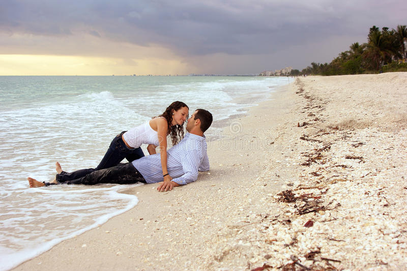 Fantasy woman about to kiss man on beach at sunse stock photography
