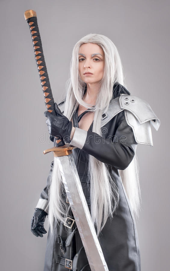 Fantasy woman warrior. Woman warrior with sword and armor isolated on the gray background stock photography