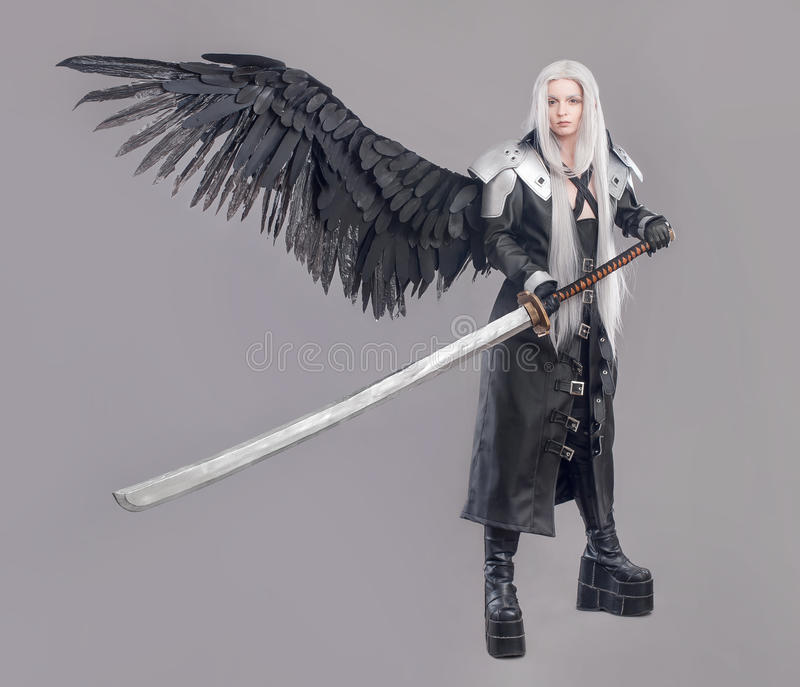 Fantasy woman warrior. Woman warrior with sword and wings isolated on the gray background stock image