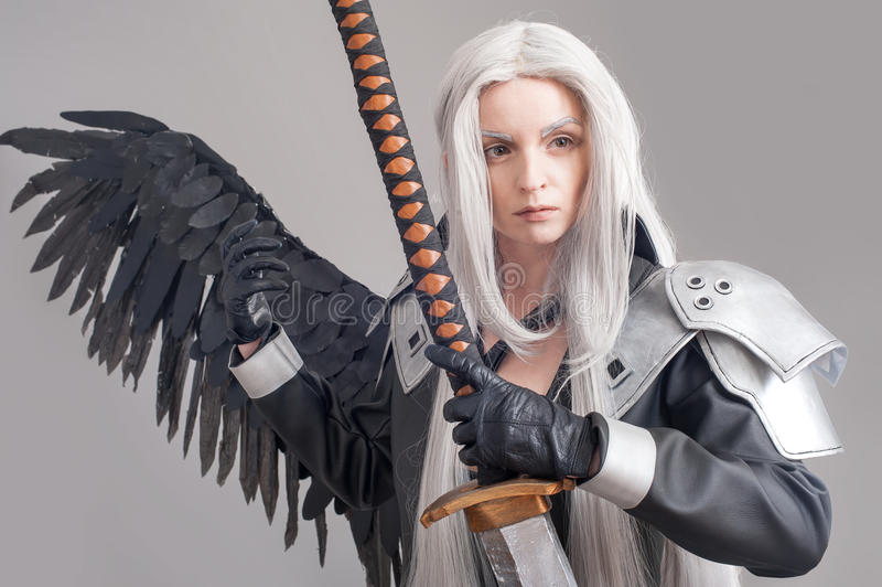 Fantasy woman warrior. Woman warrior with sword and wings isolated on the gray background royalty free stock photo