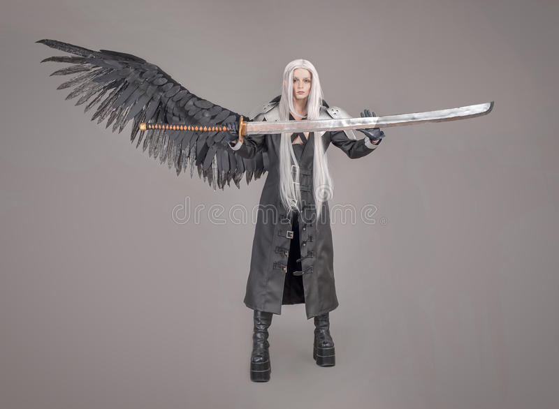 Fantasy woman warrior. Woman warrior with sword and wings isolated on the gray background stock photography