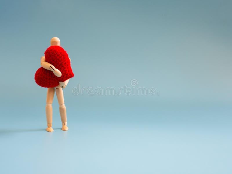 Fantoche de madeira que está e que guarda um coração vermelho no fundo de tela azul Fantoche de madeira que guarda o coração com  foto de stock