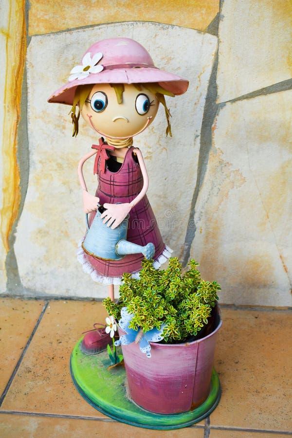 Fantoche de sorriso feito no aço colorido que mostra a uma lata molhando da menina vesgo feliz uma cubeta com uma planta verde em foto de stock royalty free