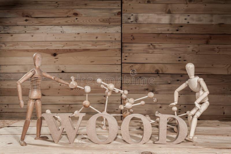 fantoches de madeira com palavra do átomo fotografia de stock