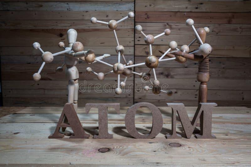 fantoches de madeira com palavra do átomo imagem de stock