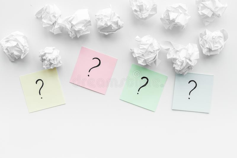 FAQ concept. Question mark on sticky notes near crumpled paper on white background top view copy space. FAQ concept. Question mark on sticky notes near crumpled royalty free stock photo