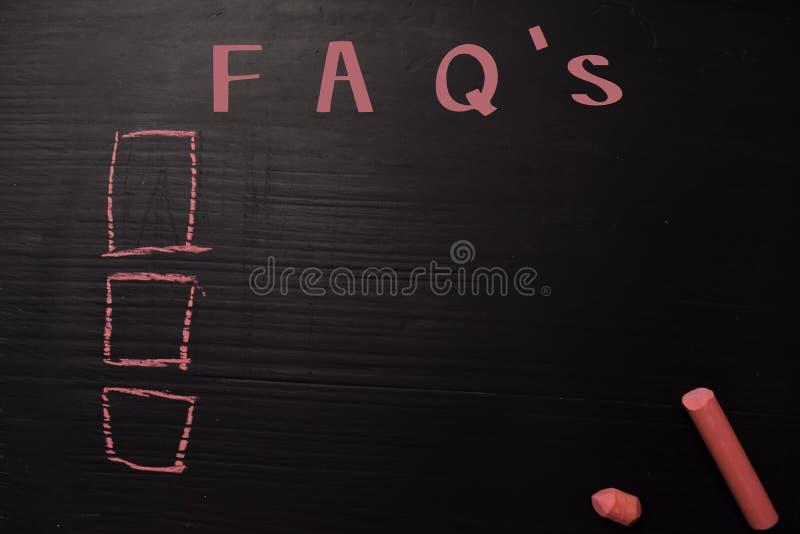 FAQ met kleurenkrijt dat wordt geschreven Gesteund door de extra diensten Bordconcept stock foto's