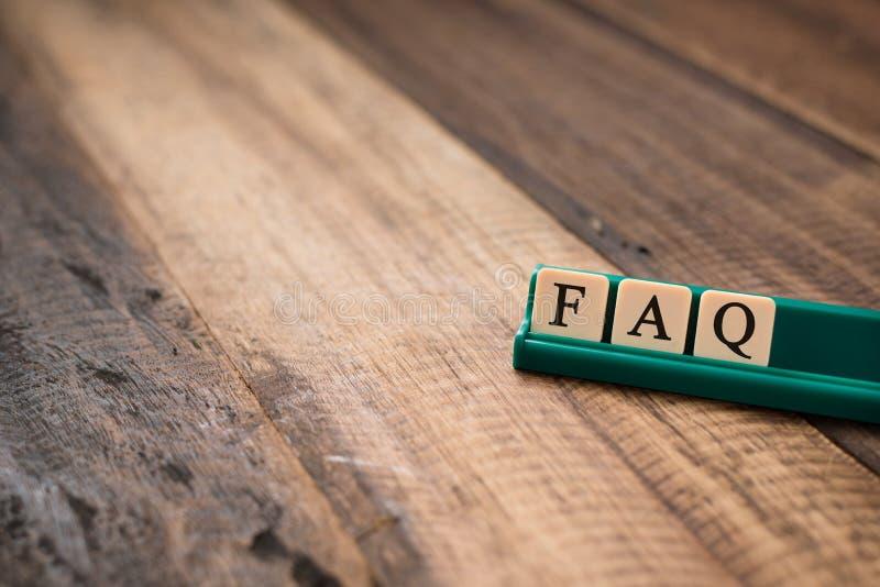 Faq-ord på alfabettegelplattor på trätabellen fråga vanligt frågebegreppet royaltyfria foton
