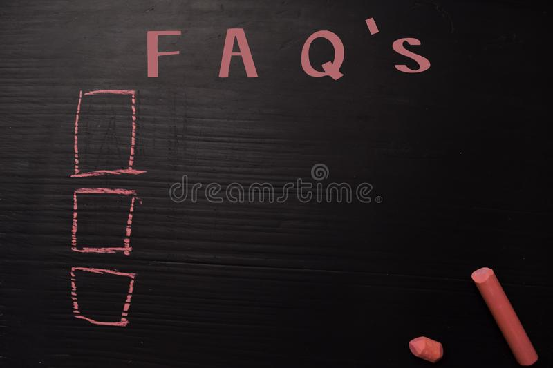 FAQ`s written with color chalk. Supported by an additional services. Blackboard concept stock photos