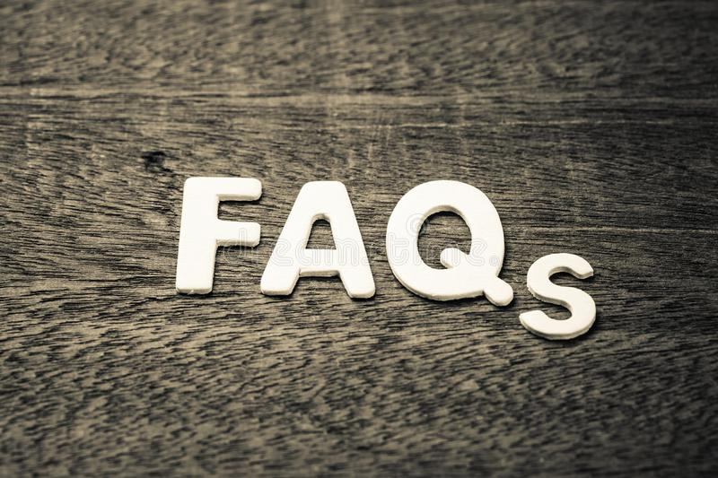 FAQs Wood Letters. FAQs abbreviation arranged by wood letters on wood texture stock image