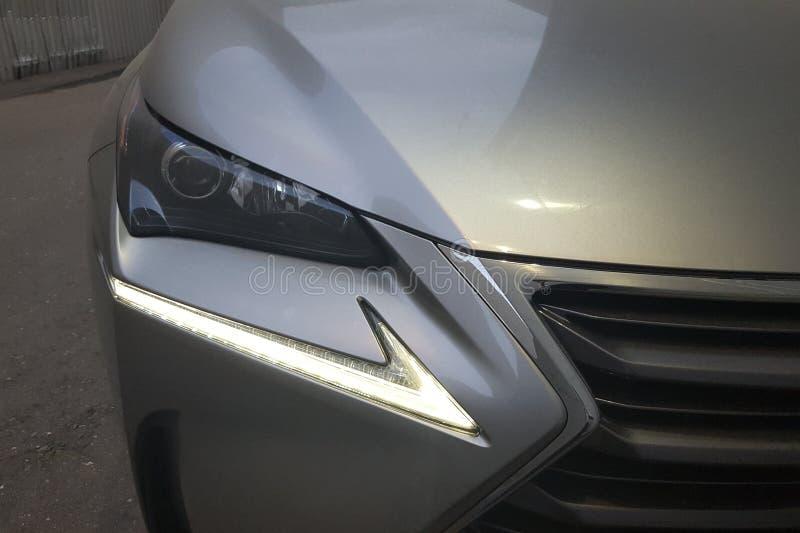Faróis conduzidos do carro luxuoso metálico de prata do suv de japão fotografia de stock