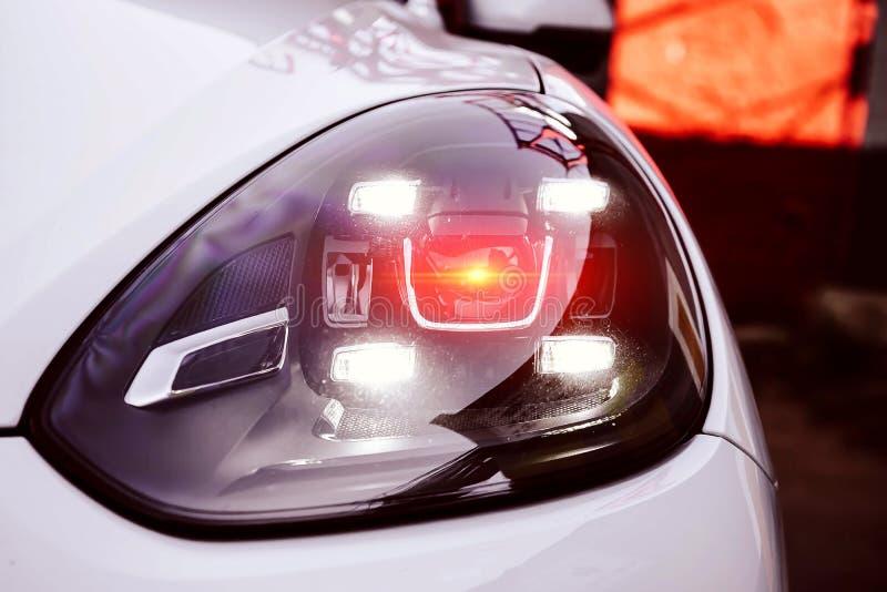 Faróis conduzidos esquerdos de um suv superior branco Com iluminação alaranjada vermelha da lente Nova gera??o de luz do carro Cl foto de stock