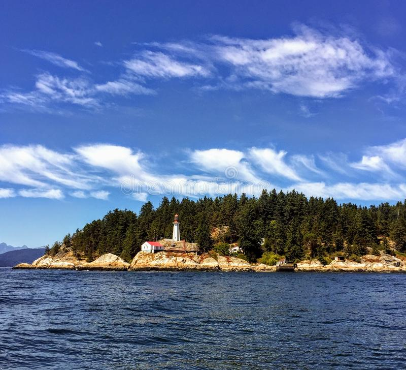 A far away view of the Point Atkinson Lighthouse in West Vancouver, British Columbia, Canada. The lighthouse is red and white and sits along a rocky point stock photos