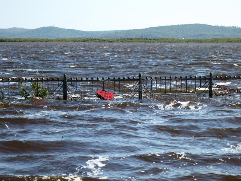 Far East of Russia. Amur river. Flooding in the Khabarovsk Territory. Embankment of the city of Komsomolsk-on-Amur. Flooded completely, Fence under water royalty free stock photos