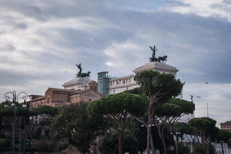 Far view of the monument to Victor Emmanuel II Piazza Venezia hide by the traditional Tuscan trees stock photo