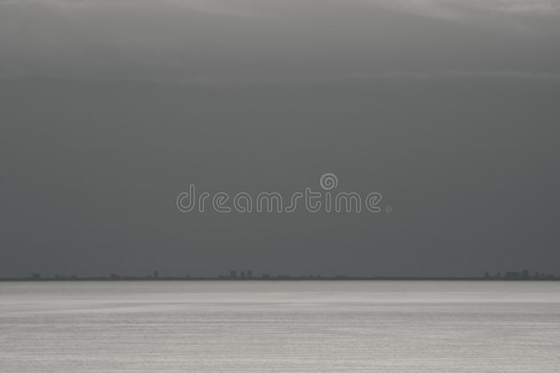Far view on silhouette city of grado above horizon in black and white from Piran, Slovenia. Far view on silhouette city of grado above horizon in black and white royalty free stock photo
