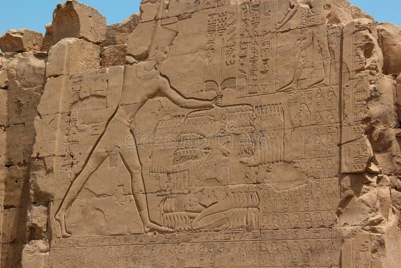 Farao som rymmer en grupp av hans besegrade fiender vid rep runt om deras halsar, innan att döda dem med ett vapen i hans assiste arkivbild
