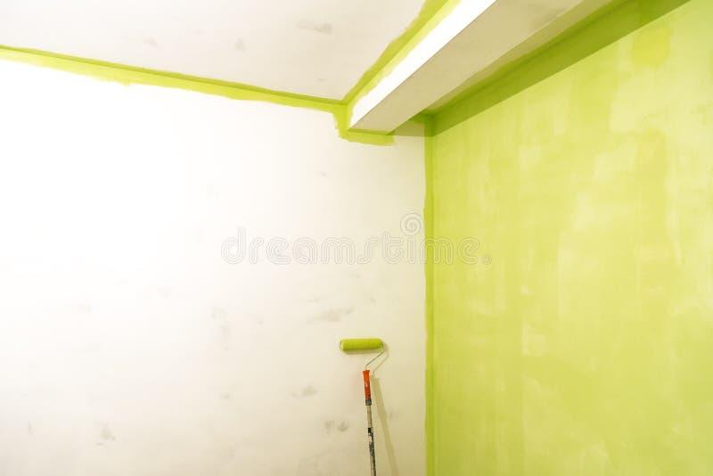 Farba rolownik blisko ściana malującej zieleni zdjęcia stock