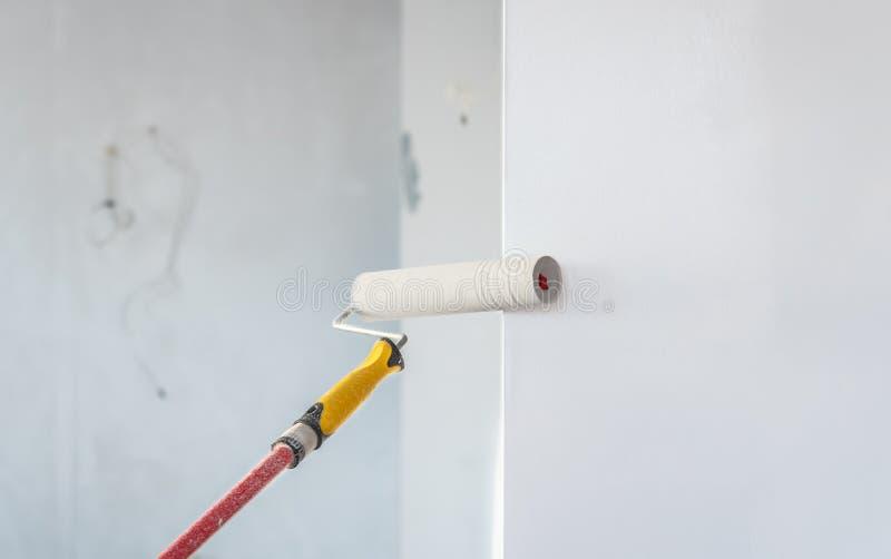 Farba rolownik stosuje farbę na biel ścianie obraz stock
