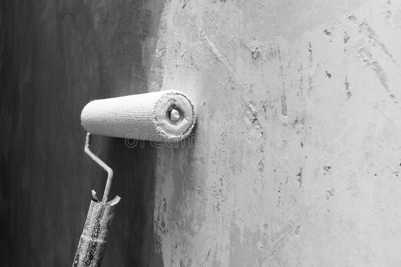 Farba rolownik stosuje farbę na biel ścianie, domowi ulepszenia fotografia stock