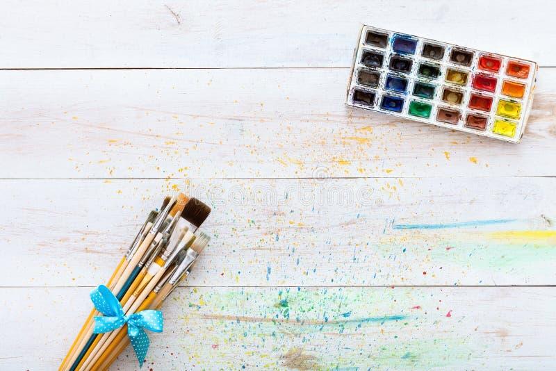 Farba szczotkuje set i pudełko z akwarelami na białym drewnianym pobrudzonym stole z pluśnięciami, artystyczny brezentowy tło, na zdjęcia royalty free
