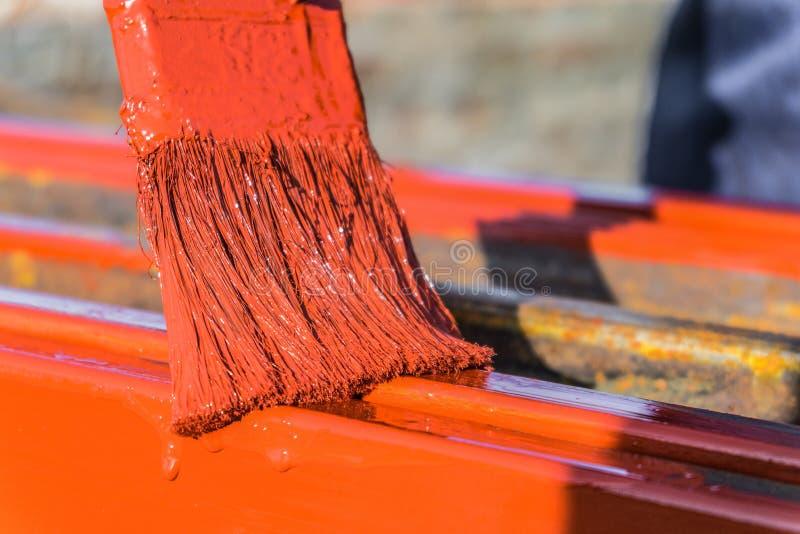 Farbauftrag durch Bürste auf Metallbauten Schützende Beschichtung von geschlossenen Stahlprofilen mit Zündkapseleisenoxidrot lizenzfreie stockfotos