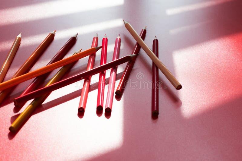 Farbbleistift und orange Ton auf dem roten Schattenhintergrund, abstrakt lizenzfreie stockfotografie