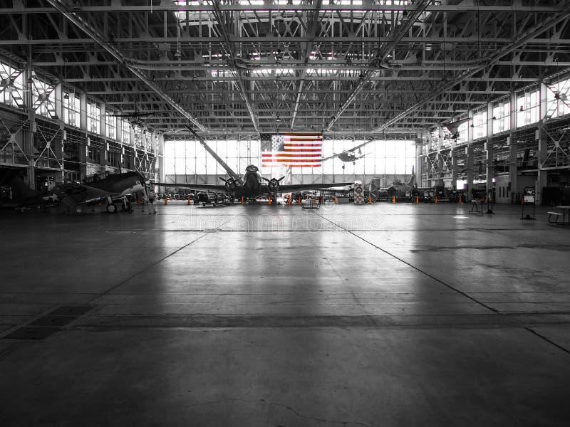 Farbe der amerikanischen Flagge im Schwarzweiss-Hintergrund-Flugzeug-Hangar stockfoto