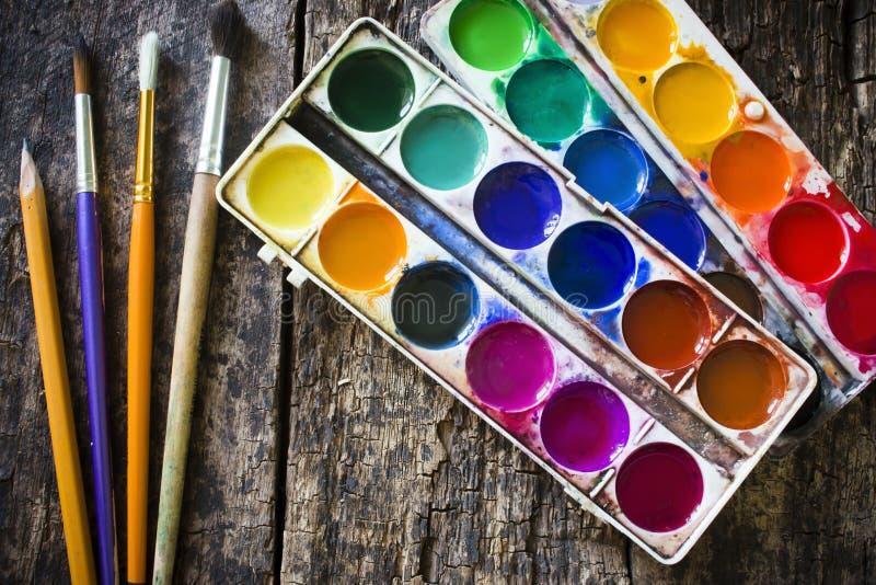 Farbe mit zwei Aquarellen und Bleistift, unterschiedlicher auf einem alten hölzernen zu malen Fächerpinsel, stockfotografie