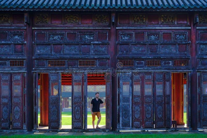 Farbe/Vietnam, 17/11/2017: Mannstellung nahe bei dekorativen Türen in einem traditionellen pavillion im Zitadellenkomplex in der  lizenzfreies stockfoto