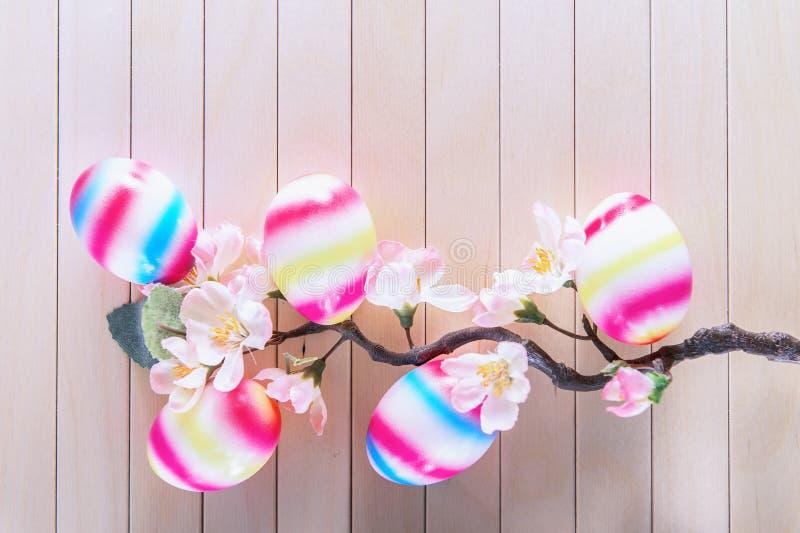 Farbeier im Eihalter auf einer Tabelle mit Tulpen lizenzfreies stockfoto